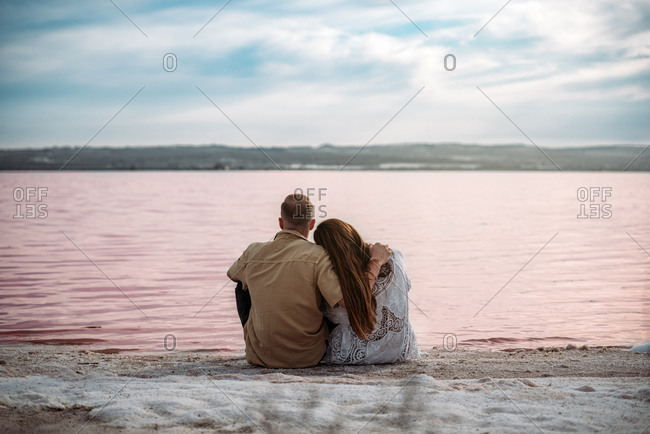 adorable couple sitting on an amazing beach of pink water and blue sky holding hands