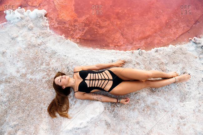 From above of calm sensual female traveler in black stylish swimsuit lounging in sun on rocky beach of pink lake at Alicante in Spain