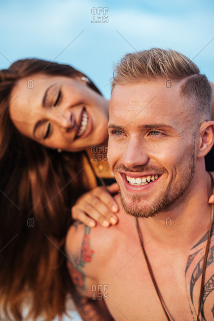 Female tourist with long hair and radiant smile sitting on back of content male undressed tattooed boyfriend looking away with sky on background at Spain