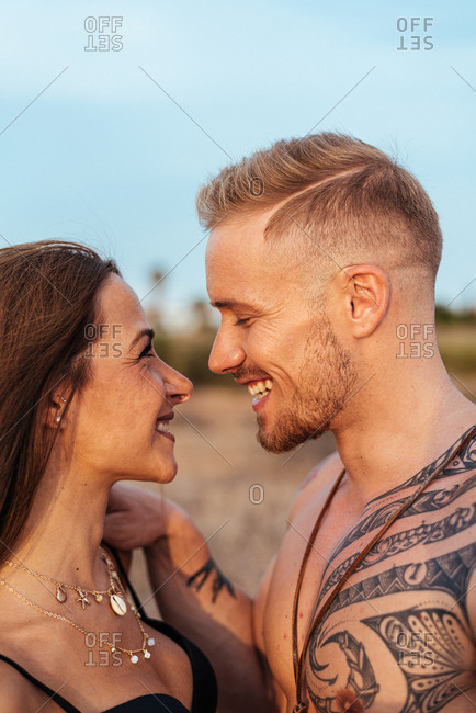 Brutal shirtless tattooed male and sensual woman in swimsuit standing close and looking away with blue sky on background at Spain