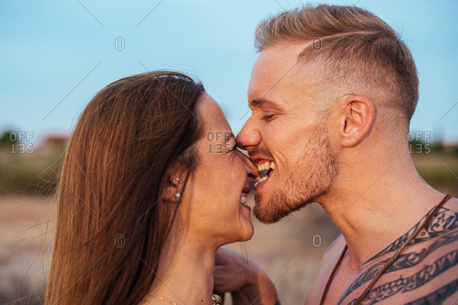 Brutal shirtless tattooed male and sensual woman biting nose in swimsuit standing close and looking away with blue sky on background at Spain