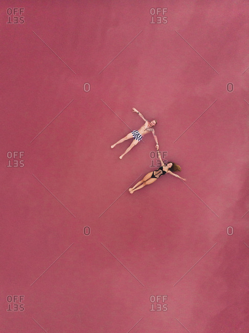 Aerial view of peaceful man and woman in swimsuits holding hands while floating on pink salty water of lake at Torrevieja at Spain