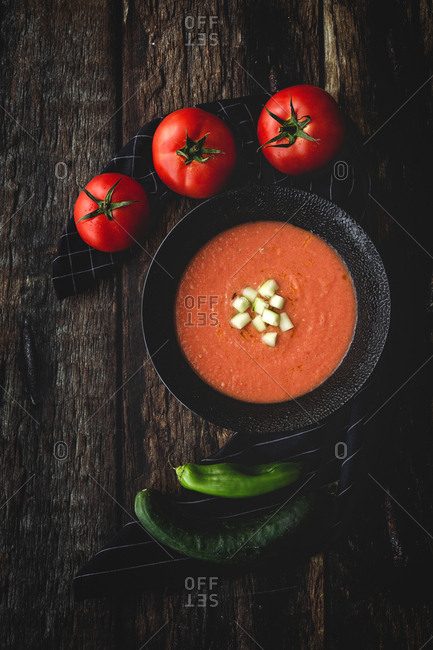 Homemade typical Spanish gazpacho from above. Salmorejo. Tomato soup with cucumber; Green pepper, bread and olive oil on dark wood background. Spanish food. Flat lay.
