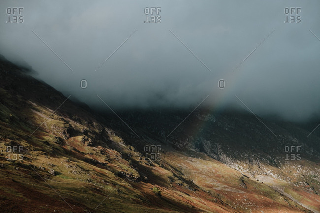 Wilderness scenery of rocky hills covered by thick mist and dim rainbow in Scotland