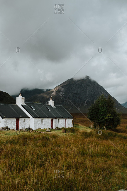 Lonely white farmhouse in autumn field in valley in Scotland surrounded by rocky hills