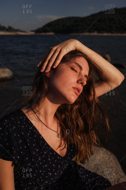 Sensual woman resting on lake shore