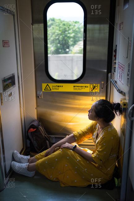 Cheerful female traveler in stylish dress at train