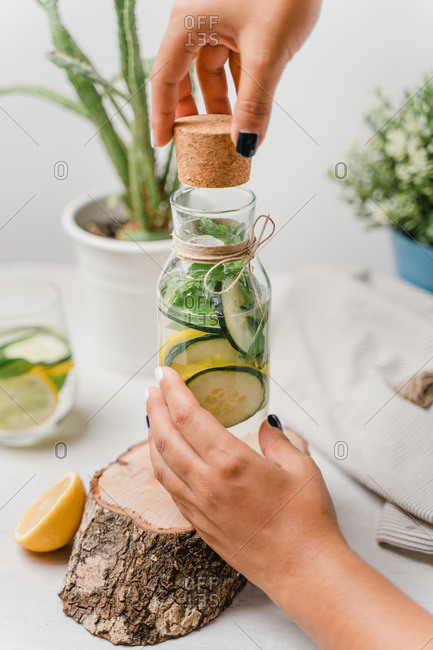 Crop woman opening glass jar of tasty lemonade with slices of fresh lemon and cucumber with green leaves of mint on wooden tray while working at white table