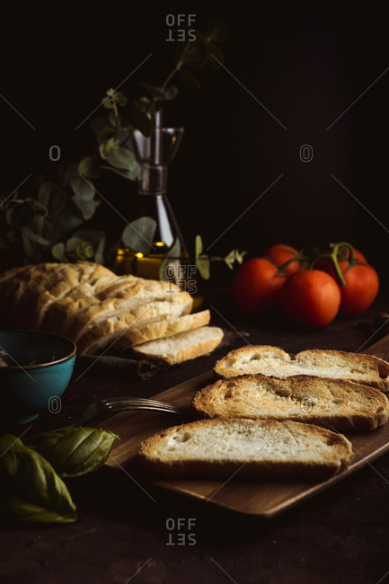 Pieces of fresh bread placed on table near fresh tomatoes and basil leaves on black background