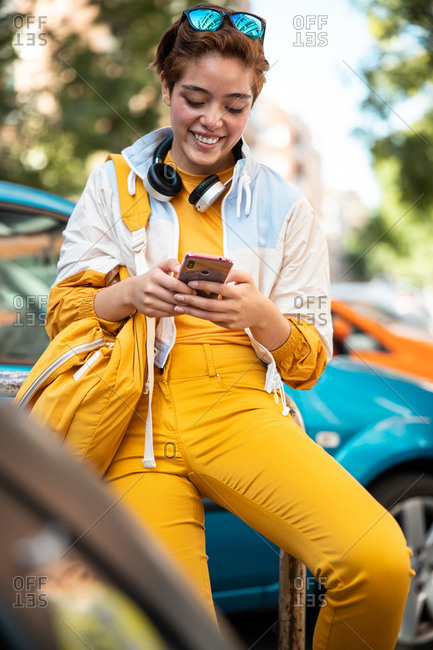 Modern teen female in yellow trendy clothes with wireless headphones and yellow handbag surfing mobile phone while sitting on fence against colorful cars and blurred modern buildings in city
