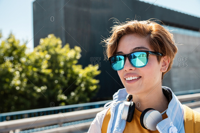 Bright millennial female in stylish sunglasses and vivid white and yellow outfit wearing wireless headphones and enjoying view while looking away against blurred city street