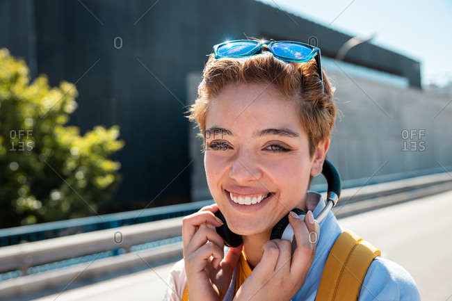 Magnificent slender stylish millennial woman with amazing green eyes and toothy smile in white and yellow clothes with wireless headphones and sunglasses looking at camera against blurred road in sunny day