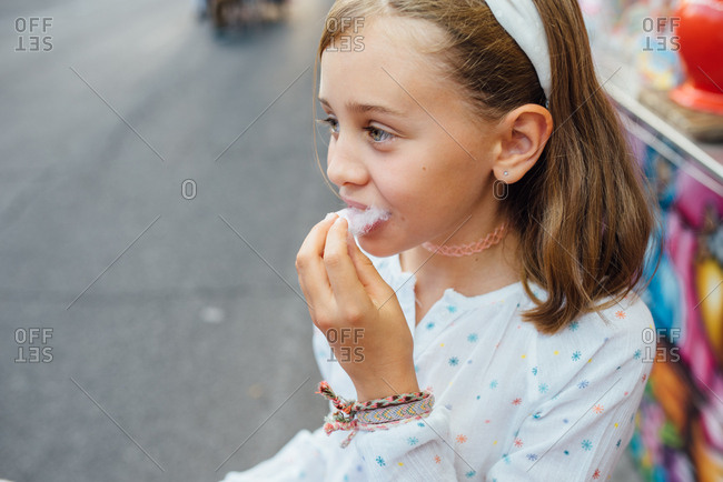 Cheerful girl eating cotton candy on street