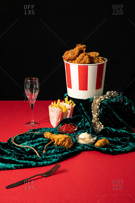Deep fried chicken and portions of french fries in composition with sauces and golden jewelry on shiny green velvet on red table on background of black wall
