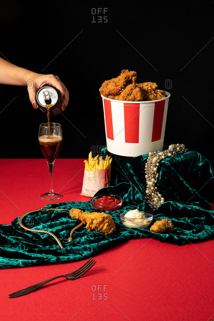 Crop female pouring sweet soda from can into wineglass beside luxurious golden jewelry and portions of fried chicken drumsticks and french fries in composition with ketchup and mayonnaise on green velvet against black wall