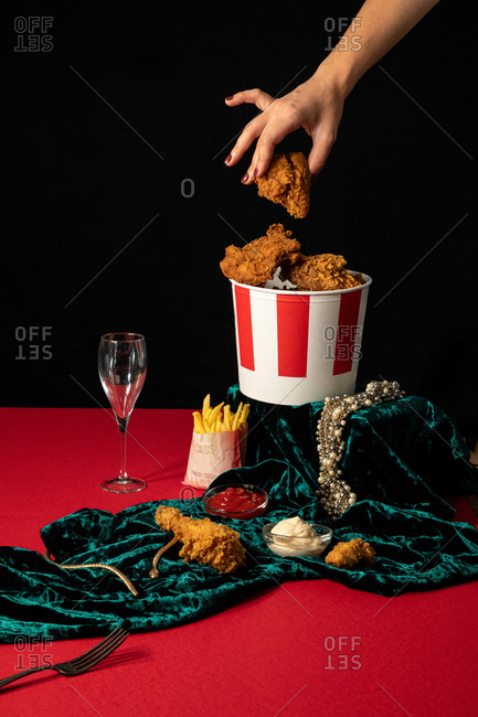 Crop woman taking fried chicken nuggets from bucket on red table with golden jewelry in composition with portions of french fries and sauces on green velvet