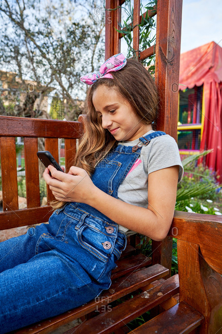 Adorable teenage girl in denim clothes smiling holding smartphone with both hands and texting with friends while sitting on wooden playground bench