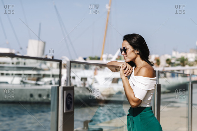 Side view of dreamy young woman with sunglasses leaning on fence and looking away on harbor dock