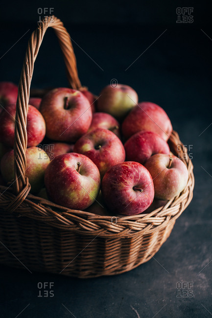 Fresh red apples on dark table and in a wicker basket on dark background