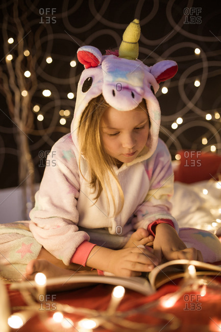 Girl reading book in bedroom decorated with Christmas lights
