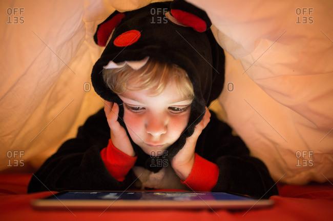 Girl using tablet under blanket