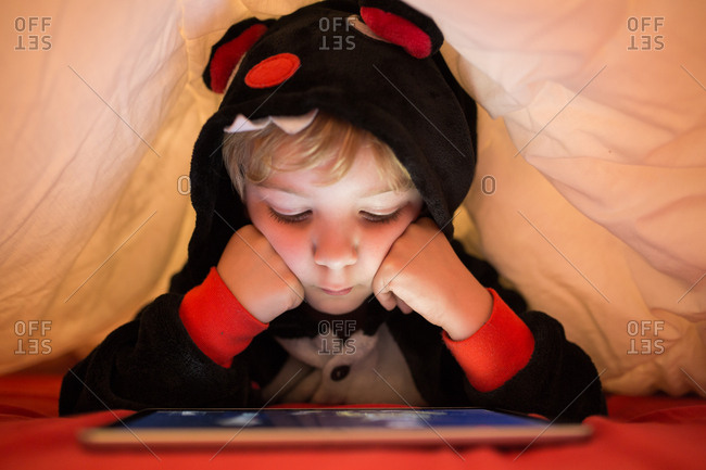 Girl using tablet under blanket