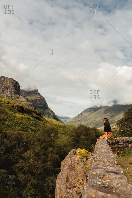 High angle side view of calm solitary woman in casual clothes sitting on stone fence and contemplating against blurred green highland in Scotland