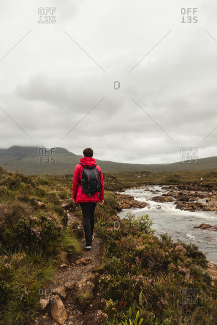 Back view of person in red and black clothes with backpack walking alone along trail near mountain river in green lush grassland against blurred misty highland in overcast weather in Scotland