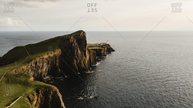 From above wonderful scenery of empty road leading across green rocky shore to solitary beacon on headland against peaceful seascape in Scotland