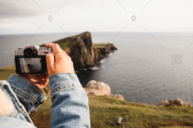 Crop person taking shot with camera of beautiful peaceful scenery of green rocky headland against calm sea waves in Scotland
