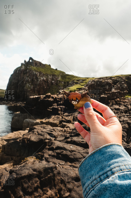Crop woman holding little figurine of highland cattle against blurred green grassy hill on rocky shore in overcast weather