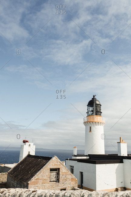 Beautiful white Dunnet Head lighthouse in Scottish highlands with blue sky and white clouds on background