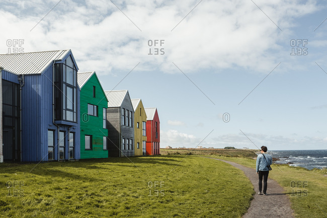Back view of male traveler walking on pathway in village with colorful houses and scenic landscape with green grass at Scottish seaside