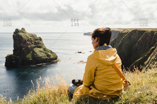 Serene tourist enjoying view of tranquil green valley in cloudy weather