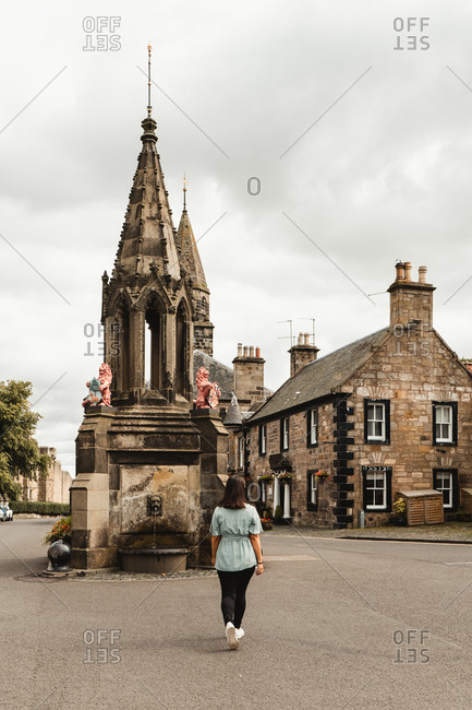 Back view of female traveler walking on old town square with beautiful medieval fountain and stone buildings during sightseeing tour in Scotland
