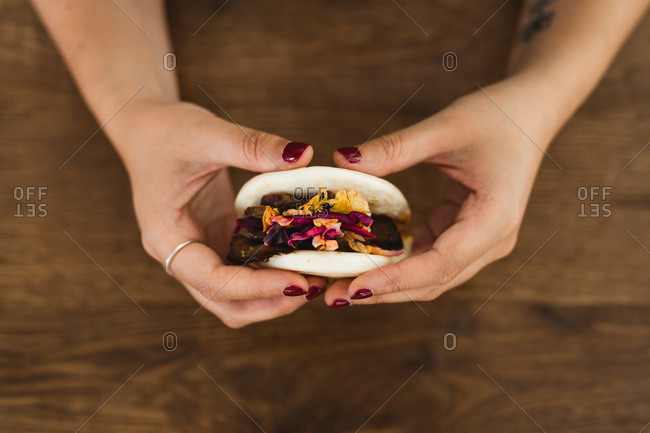 From above of crop hands of woman holding traditional Asian sandwich steamed bun with meat and vegetables over wooden table with bamboo steamer