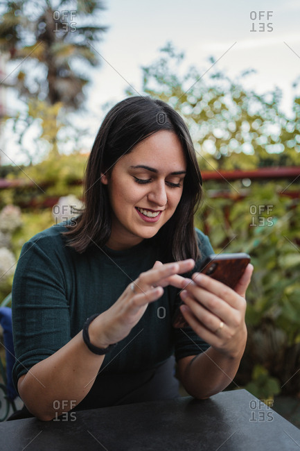 Young brunette in casual clothes browsing internet on smartphone and laughing at funny photo while resting on terrace with green plants on background