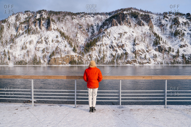 Back view of female in warm red jacket standing next to fence on bank of Siberian river with magnificent snowy mountains on other side on winter day