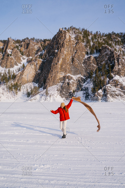 Happy female in red jacket running with scarf in raised hand on snowy valley with majestic rocks on background and enjoying sunny winter day in Siberia Russia