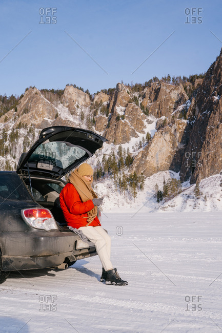Side view of female in warm active wear sitting on open car trunk and using phone in snowy valley with beautiful rocks during winter road trip in Siberia Russia