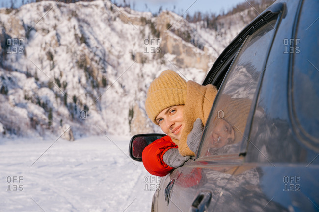 Happy smiling young female traveler in warm clothes sitting in car and leaning out window during road trip to snowy mountains in Siberia Russia