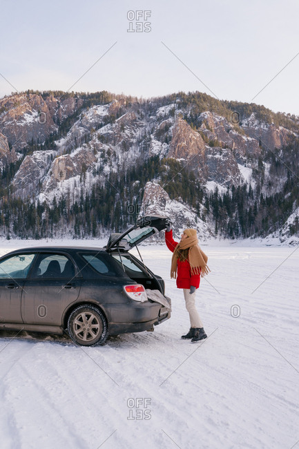 Side view of active woman in warm clothes opening car trunk while standing in snowy valley next to majestic rocks in Siberia Russia