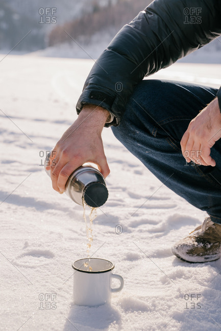 Man pouring tea from thermos bottle on winter day