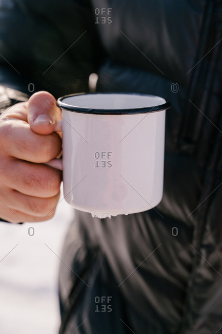 Crop male traveler in warm black jacket holding white enamel mug with hot tea while standing outdoors on winter day in Siberia