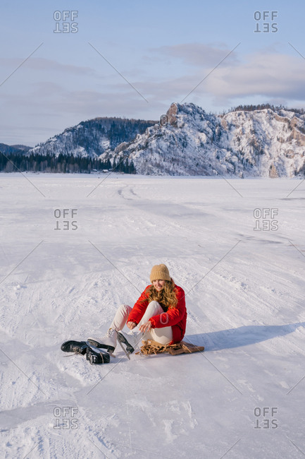 Woman sitting on snow and changing boots