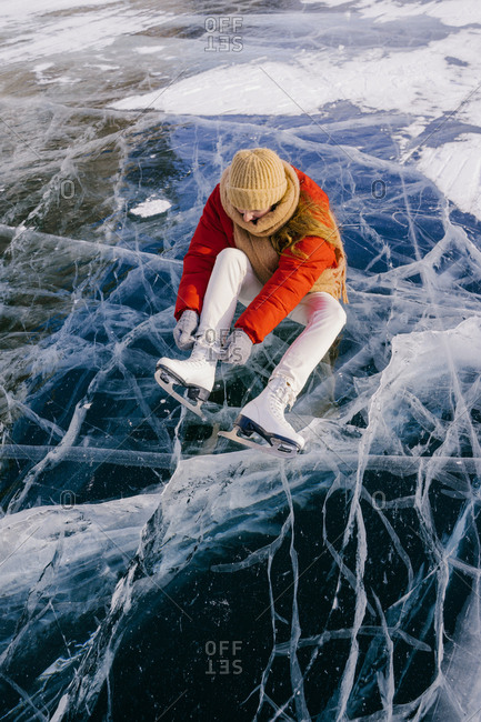 Woman sitting on frozen river and tying the shoelaces