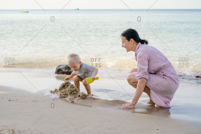 Toddler and mother playing with sand on beach against blurred seascape in sunny day
