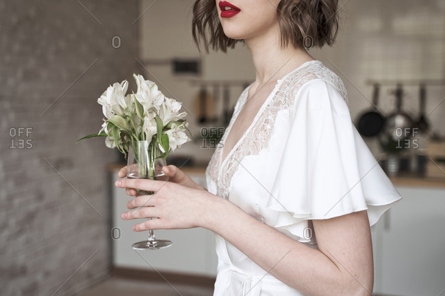Charming modest lady in white dress with lace looking away and dreaming while holding glass with small white flowers and enjoying scent