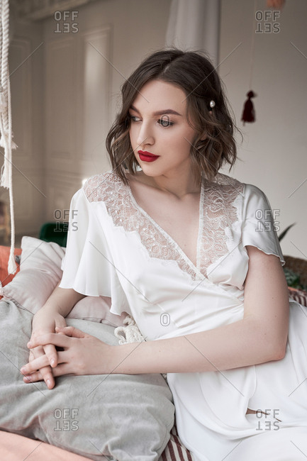Gorgeous woman with red lips in white dress looking away while sitting on floor beside sofa