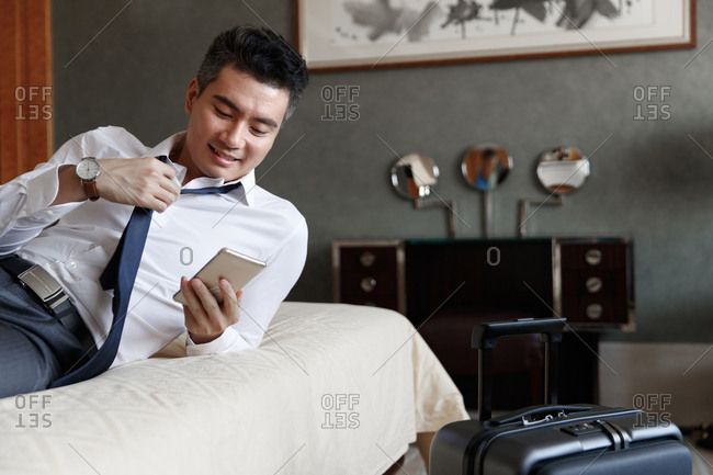 Young man lying in bed watching mobile phone